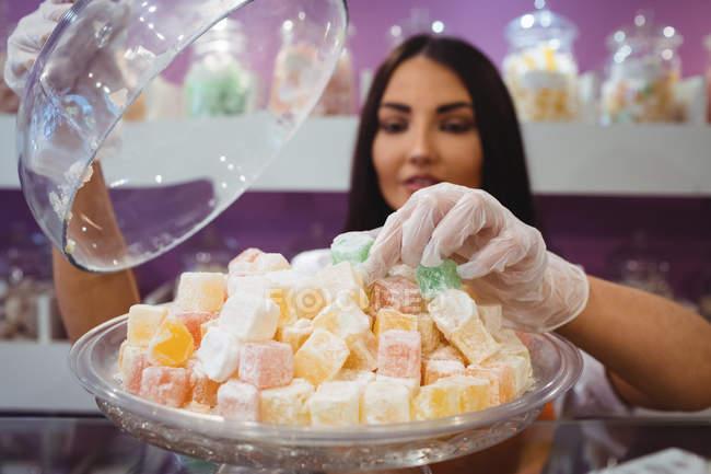 Mujer tendero arreglando dulces turcos en el mostrador en la tienda - foto de stock