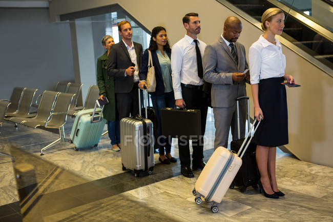 Passengers standing in a queue at airport terminal — Stock Photo