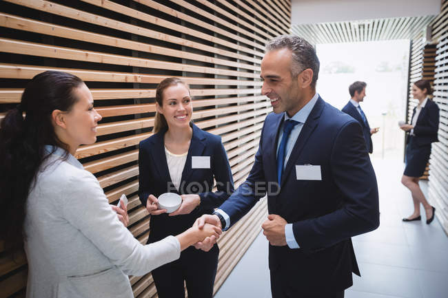 Business people having tea and interacting during break time in office — Stock Photo
