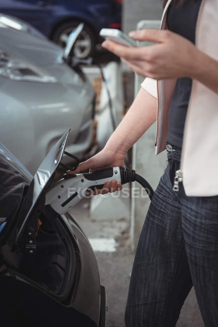Mid section of woman using mobile phone while charging electric car at vehicle charging station — Stock Photo