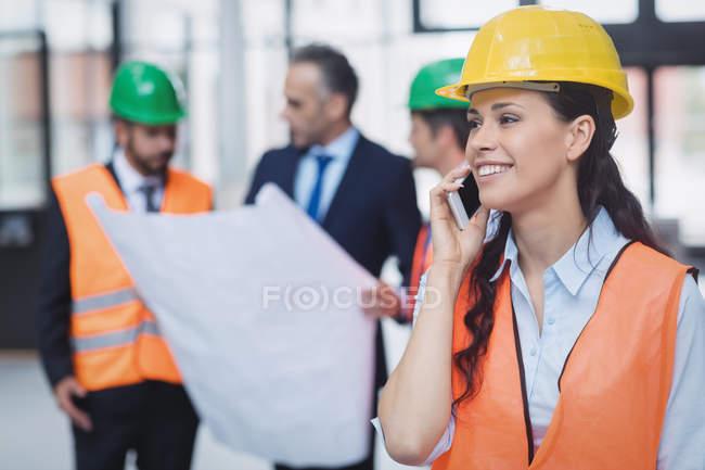 Уверенная женщина-архитектор разговаривает по мобильному телефону — стоковое фото