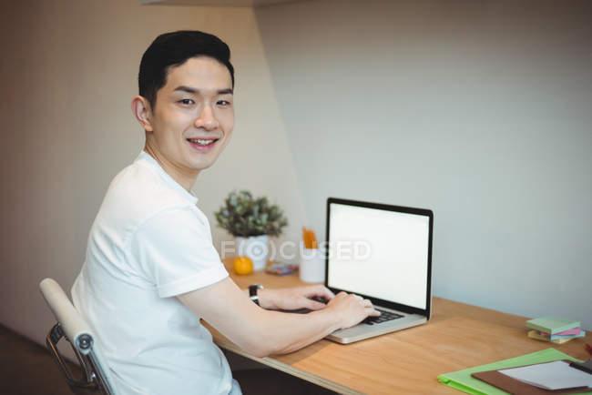 Ritratto di dirigente d'azienda sorridente che lavora su laptop in ufficio — Foto stock
