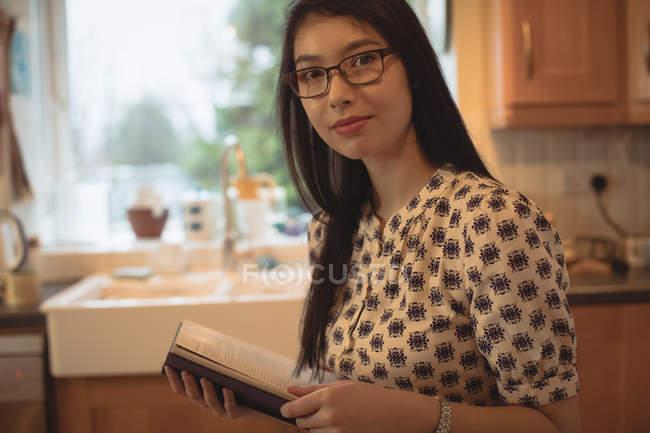 Ritratto di donna che legge un libro in cucina a casa — Foto stock