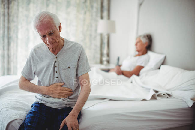 Worried senior man with hand on stomach sitting in bedroom — Stock Photo
