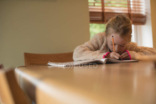 Attentif fille faire des devoirs dans le salon à la maison — Photo de stock