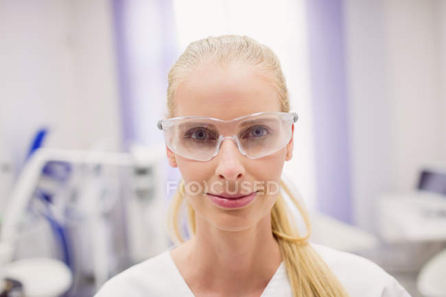 Female doctor wearing protective glasses in clinic — Stock Photo