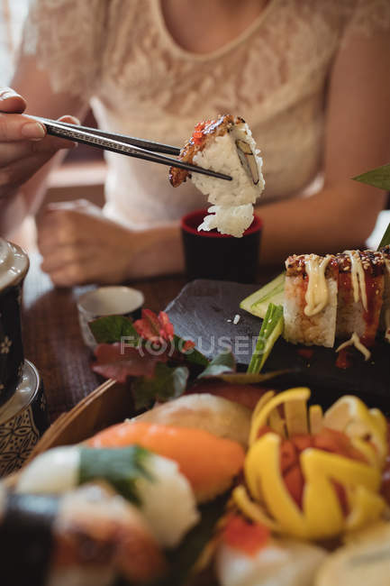 Mid section of woman having sushi in restaurant — Stock Photo