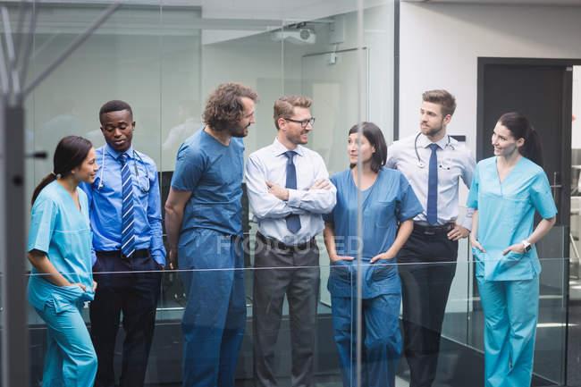 Equipe de médicos discutindo uns com os outros no corredor do hospital — Fotografia de Stock