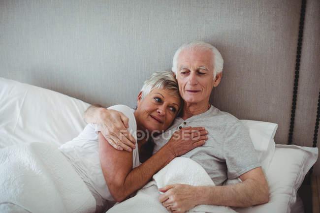 Casal sênior descansando na cama no quarto — Fotografia de Stock