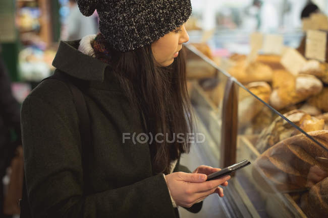 Woman using mobile phone near bakery counter in supermarket — Stock Photo