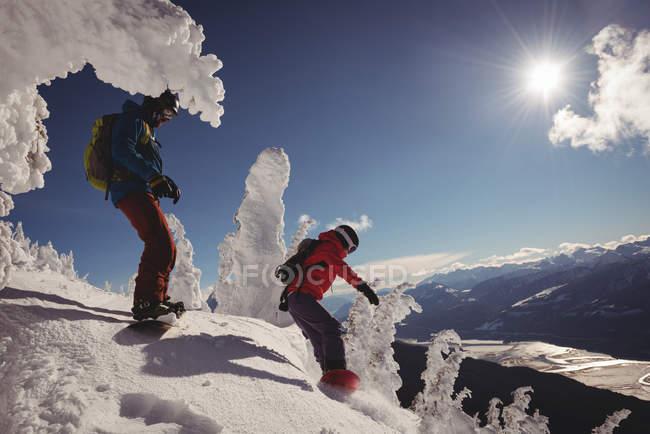 Два лыжника катаются в снежных Альпах зимой — стоковое фото