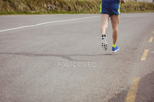 Low section of athlete running on country road — Stock Photo