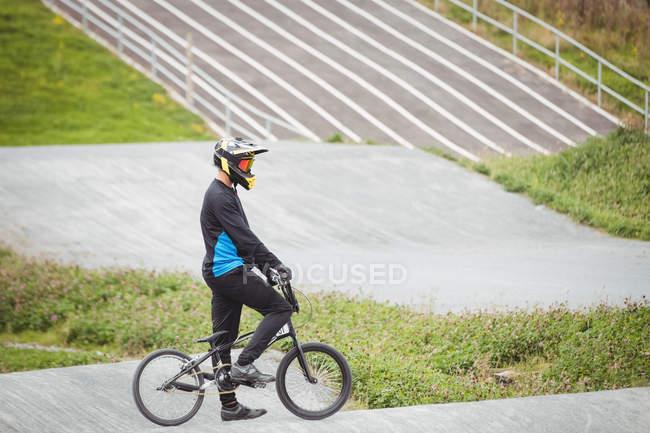 Велосипедист, стоящий на велосипеде BMX в скейтпарке — стоковое фото