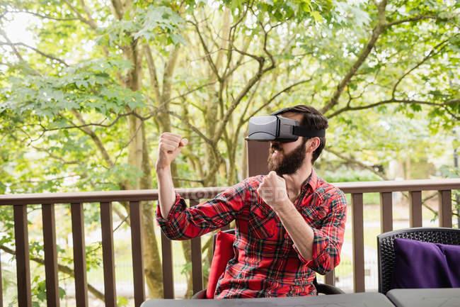 Homme utilisant casque de réalité virtuelle dans la terrasse du bar — Photo de stock