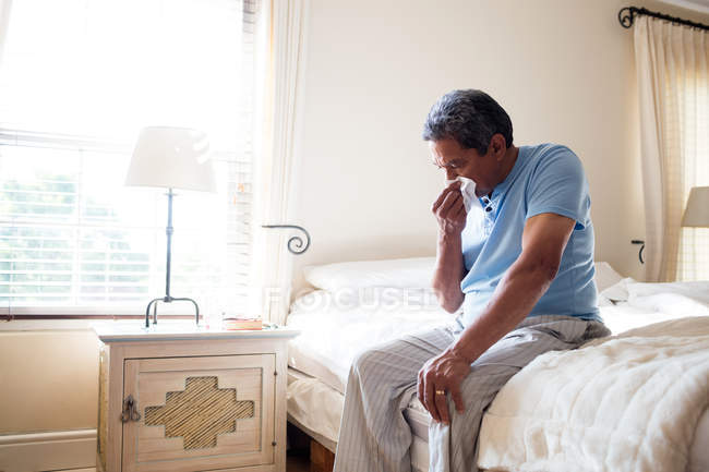 Senior man sneezing nose with handkerchief on bed at home — Stock Photo