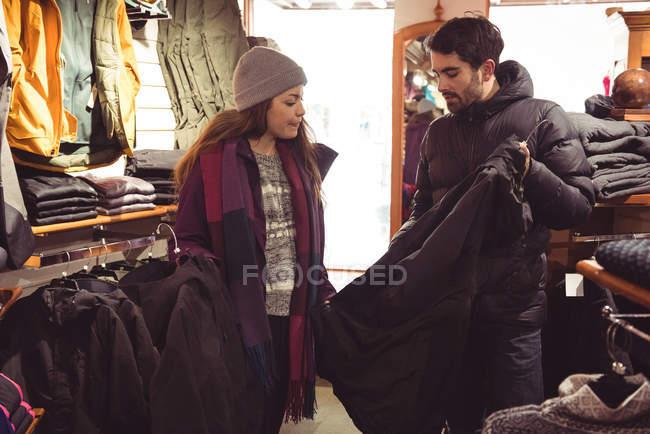 Coppia selezionando abbigliamento insieme in un negozio di abbigliamento — Foto stock
