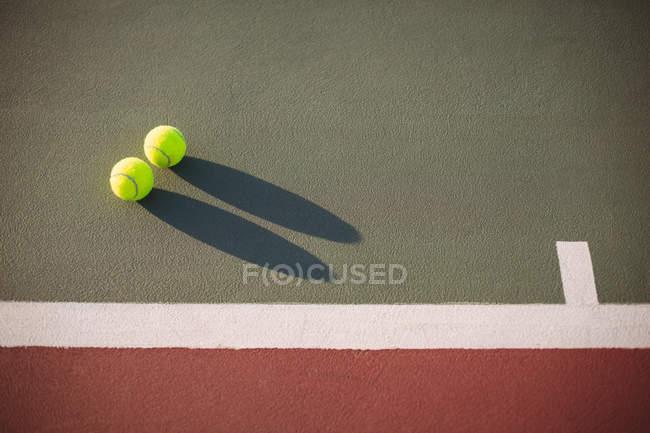 Primer plano de pelotas de tenis en cancha con sombra - foto de stock