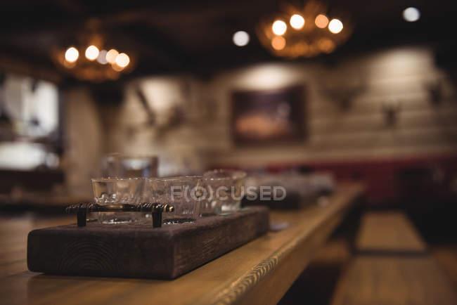 Nahaufnahme eines Holztabletts mit Gläsern auf der Theke — Stockfoto