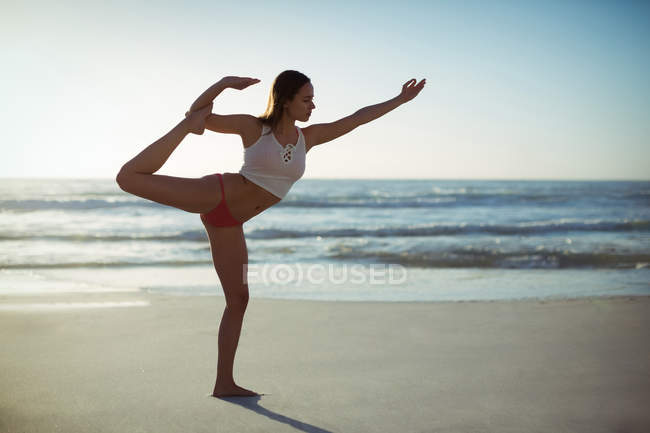 Woman performing yoga on beach on a sunny day — Stock Photo