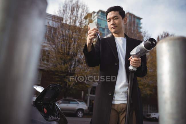 Mann benutzt Handy beim Halten von Auto-Ladegerät an Elektroauto-Ladestation — Stockfoto