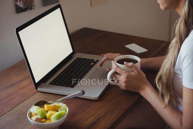 Frau benutzt Laptop beim Kaffeetrinken im Schlafzimmer zu Hause — Stockfoto