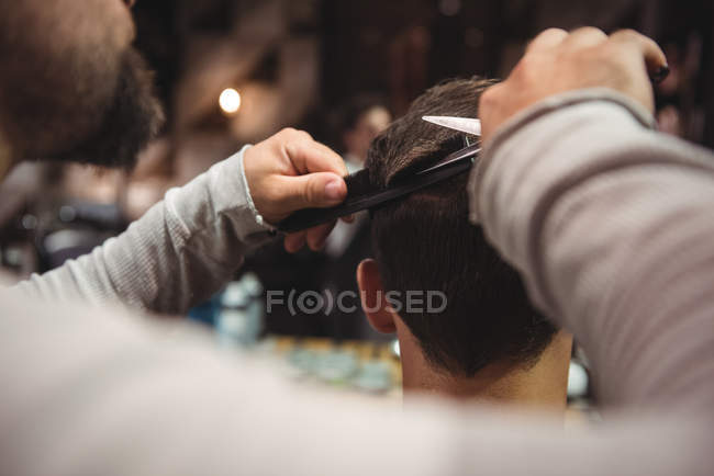 Close-up of man getting hair trimmed by hairdresser with scissors in barber shop — Stock Photo