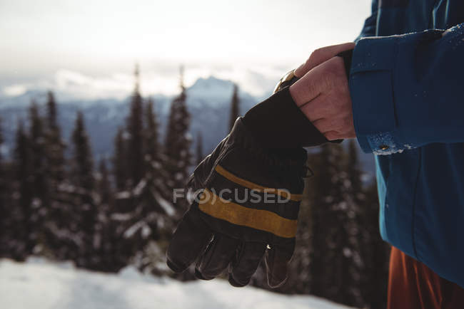 Midsection of man wearing gloves at mountain during winter — Stock Photo
