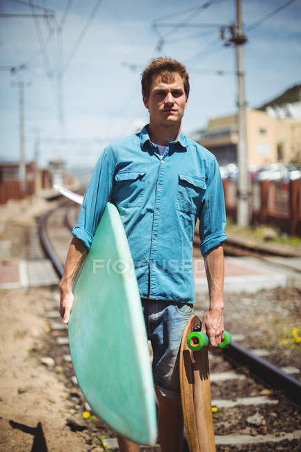 Portrait of man carrying skateboard and surfboard crossing railway track — Stock Photo