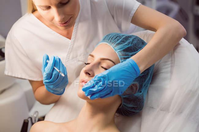 Крупный план женского пациента принимающего лица инъекции в клинике — стоковое фото