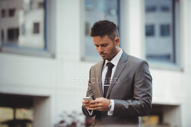 Businessman using mobile phone near office building — Stock Photo