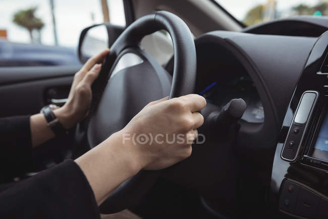 Hands of man driving electric car — Stock Photo