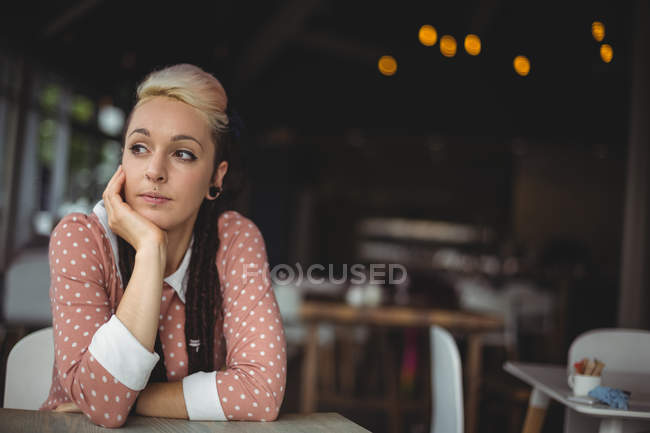 Thoughtful of woman with hand on chin in cafe — Stock Photo