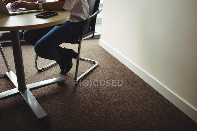 Sezione bassa di uomo d'affari che lavora su computer portatile in ufficio — Foto stock