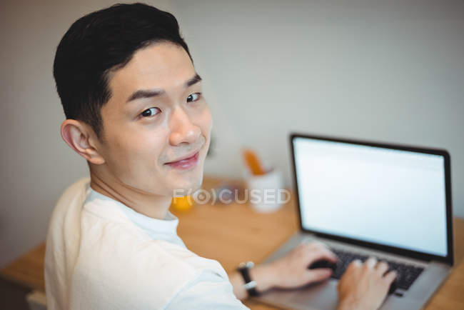 Portrait of smiling business executive working on laptop in office — Stock Photo