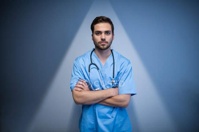 Vorderansicht eines Krankenpflegers, der mit verschränkten Armen im Krankenhausflur steht — Stockfoto