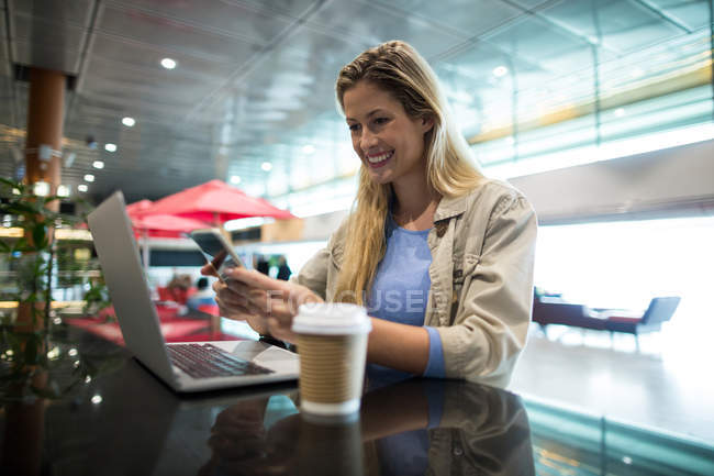 Smiling woman using mobile phone in waiting area at airport terminal — Stock Photo