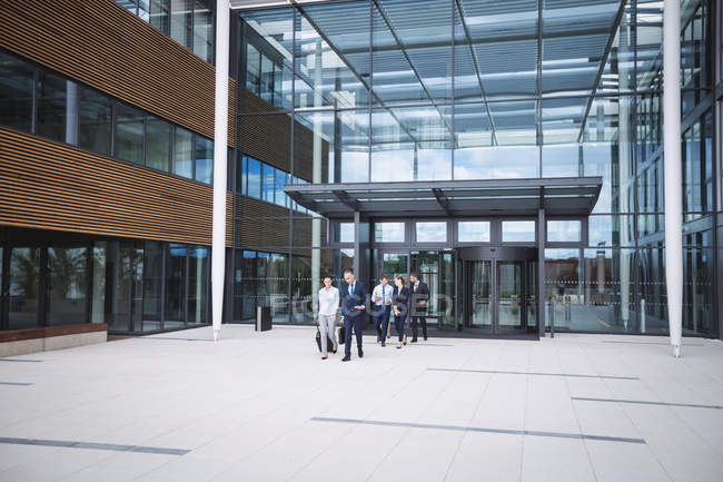 Group of business people walking outside the entrance of an office building — Stock Photo