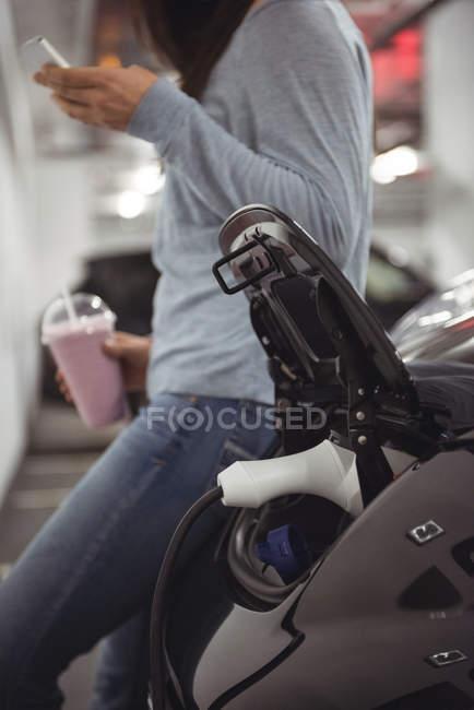 Voiture chargée avec chargeur de voiture électrique tandis que la femme debout en arrière-plan à la station de charge du véhicule électrique — Photo de stock