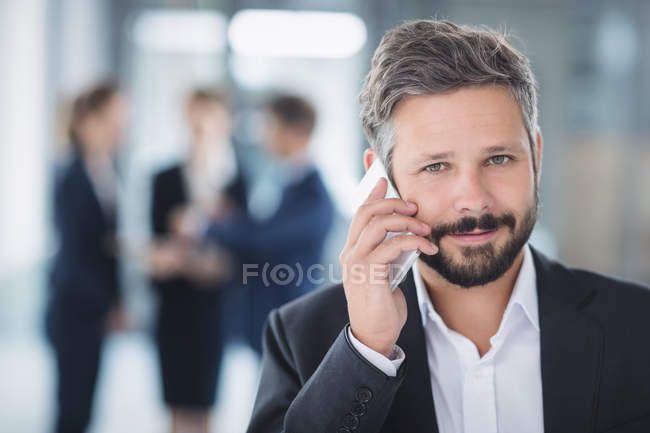 Retrato de homem de negócios falando no celular no escritório — Fotografia de Stock