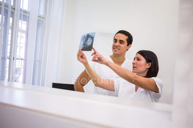 Todos discutiendo sobre informe de radiografía dental en clínica - foto de stock