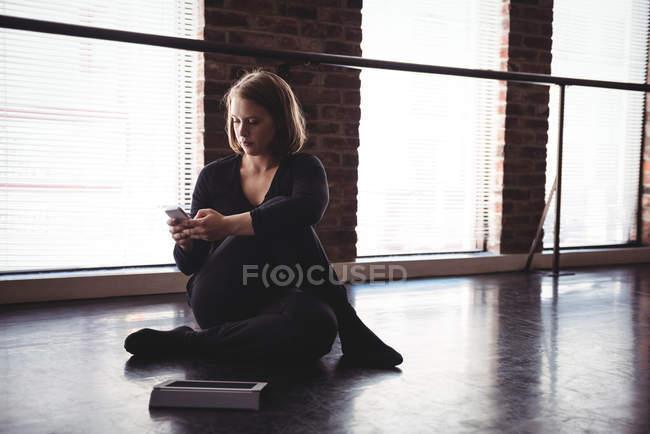 Танцюрист розтягування по підлозі і використання мобільного телефону у студії танцю — стокове фото