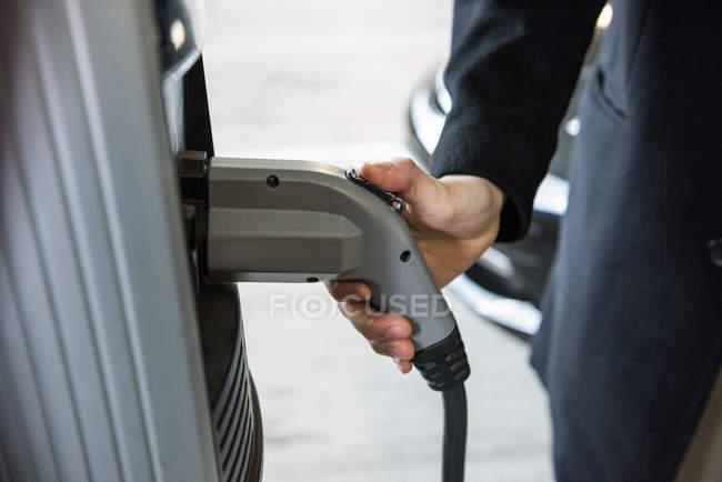 Gros plan de l'homme qui charge la voiture à la station de recharge du véhicule électrique — Photo de stock