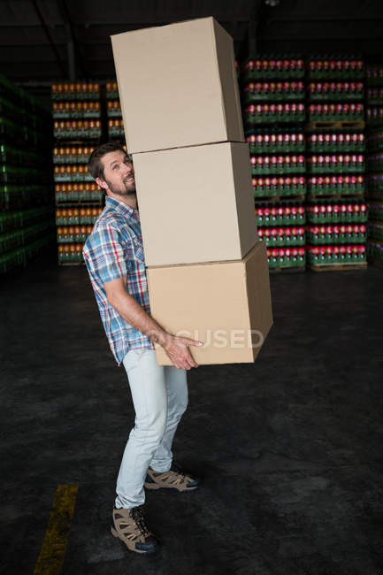 Side view of man carrying cardboard boxes in warehouse — Stock Photo