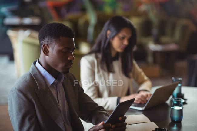 Businessman and a colleague working over digital tablet and laptop in office — Stock Photo