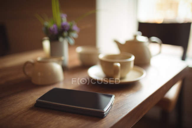 Mobile phone and coffee cup on wooden table in cafe — Stock Photo