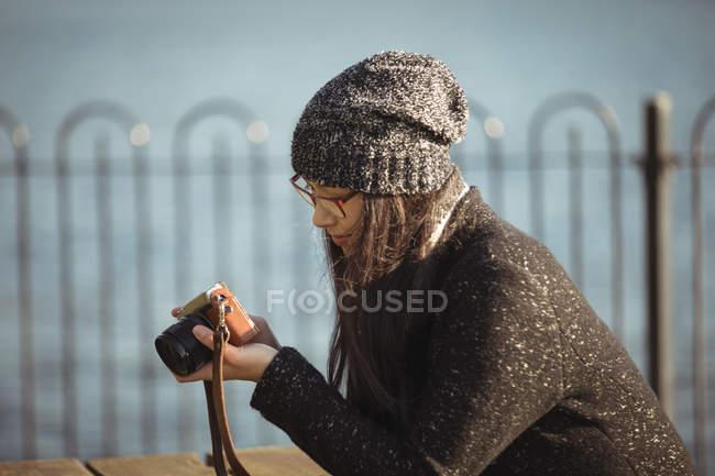 Donna che guarda le foto sulla fotocamera digitale in una giornata di sole — Foto stock
