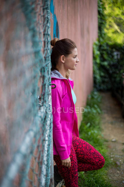 Parkour woman standing against a wall — Stock Photo