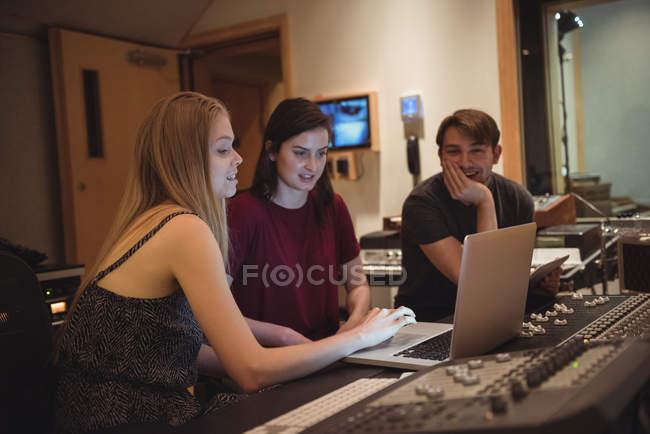 Audio engineers using laptop near sound mixer in music studio — Stock Photo