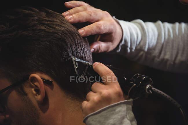 Primo piano di uomo ottenere capelli tagliati dallo stilista con trimmer in negozio di barbiere — Foto stock