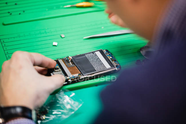 Primer plano de hombre reparar móvil en centro de reparación - foto de stock